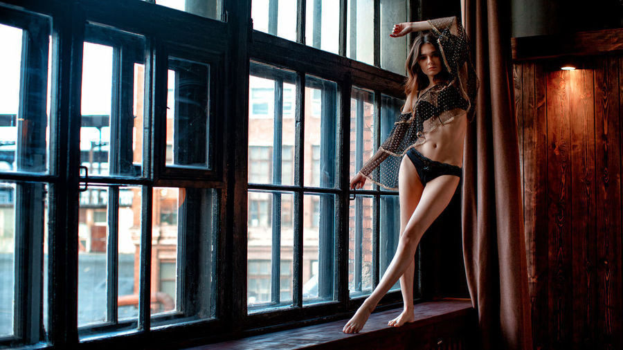 Portrait of sensuous young model wearing lingerie while standing on window sill at home