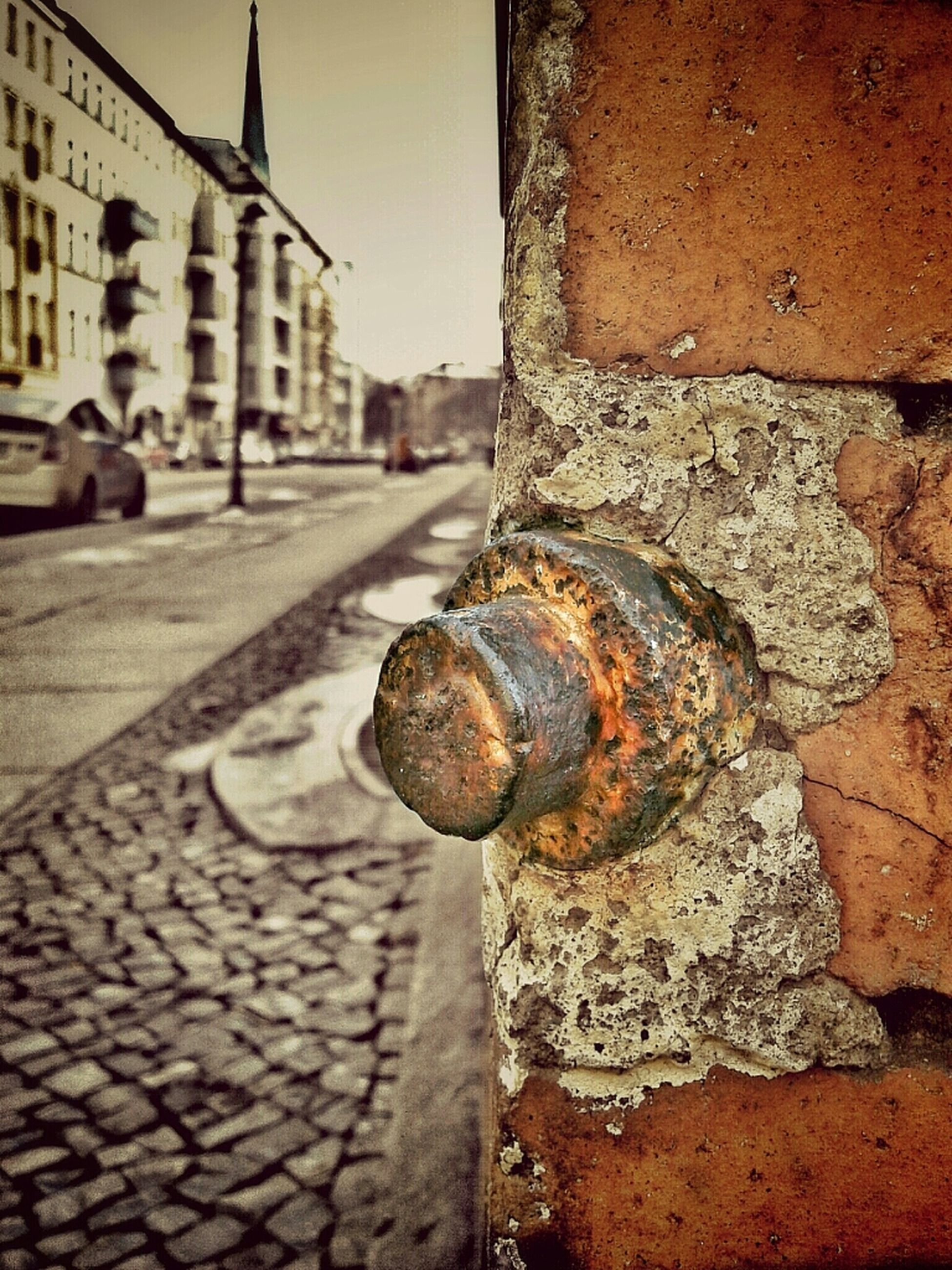 architecture, built structure, building exterior, focus on foreground, street, close-up, outdoors, day, sunlight, metal, city, weathered, building, sky, rusty, wall - building feature, old, no people, textured, road