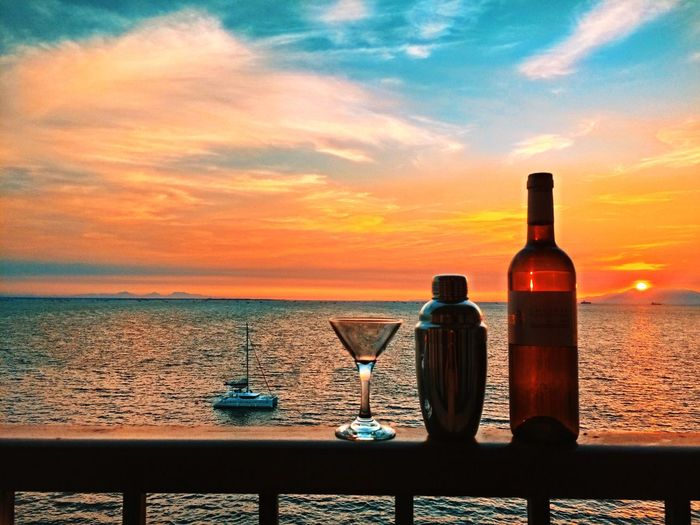 Wine bottle with cocktail shaker and glass on railing with sea in background