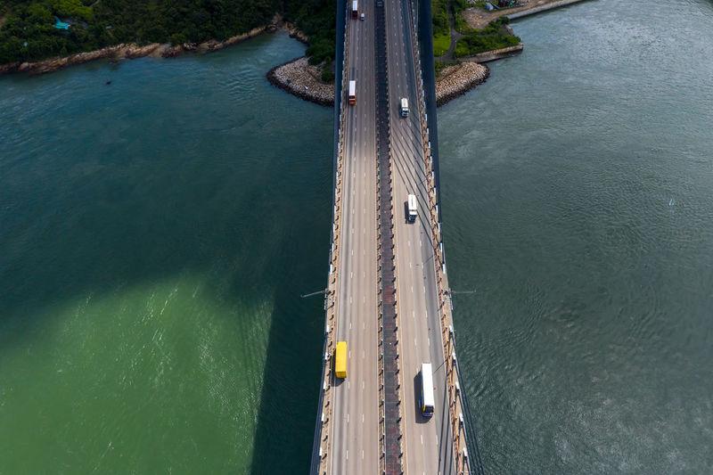 Drone view of vehicles on bridge over sea