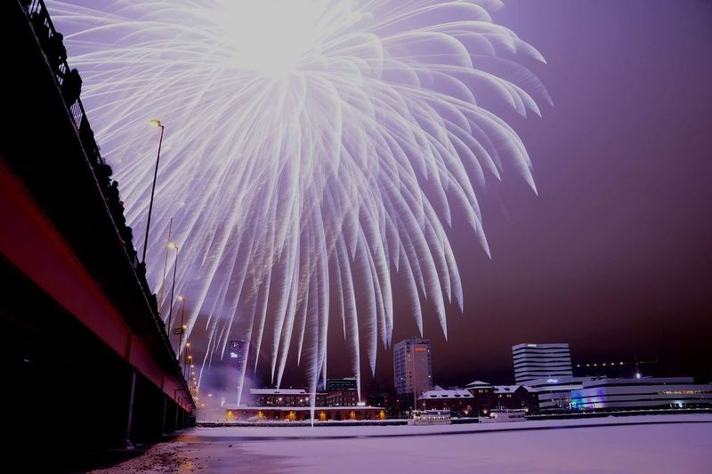 Firework display in city against sky at night