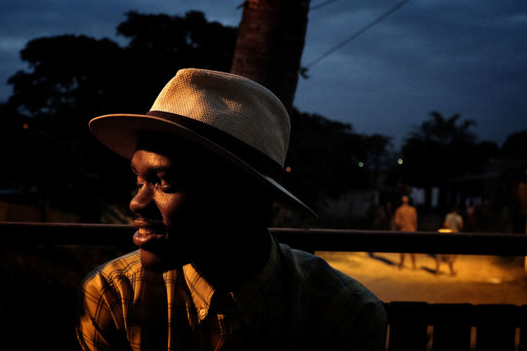 Sbo in his hometown Umlazi, South Africa's second biggest township. Portrait Headshot Hat Dark Evening Durban South Africa Umlazi Township Night People Documentary Documentary Photography Travel Fuji X100s Africa Man Light
