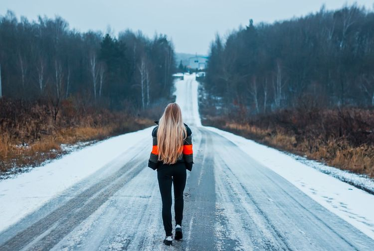 Rear view of woman on snow covered road