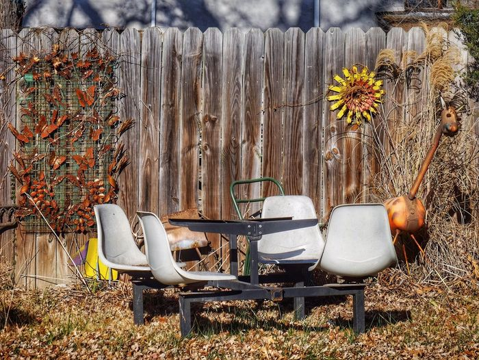 Empty chairs against wooden fence at backyard