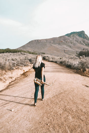 Full length rear view of woman on arid landscape