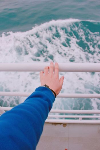 Cropped hand touching railing at boat deck