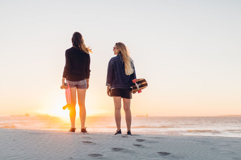 Rear view of women standing with skateboards at beach against sky