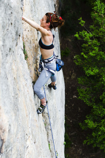 High angle view of woman climbing rock