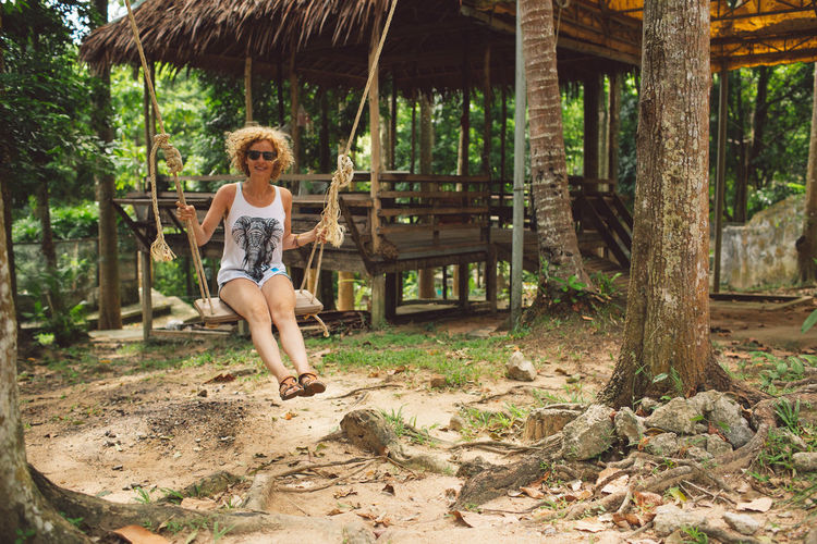 Ko Samui Thailand Curly Hair Girl Swinging Swing Full Length One Person Tree Casual Clothing Leisure Activity Day Plant Nature Lifestyles Real People Land Outdoors Childhood Enjoyment Architecture Standing Sunlight Child Shorts