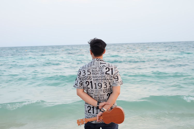 Rear View Of Young Man Holding Violin While Standing By Sea Against Sky
