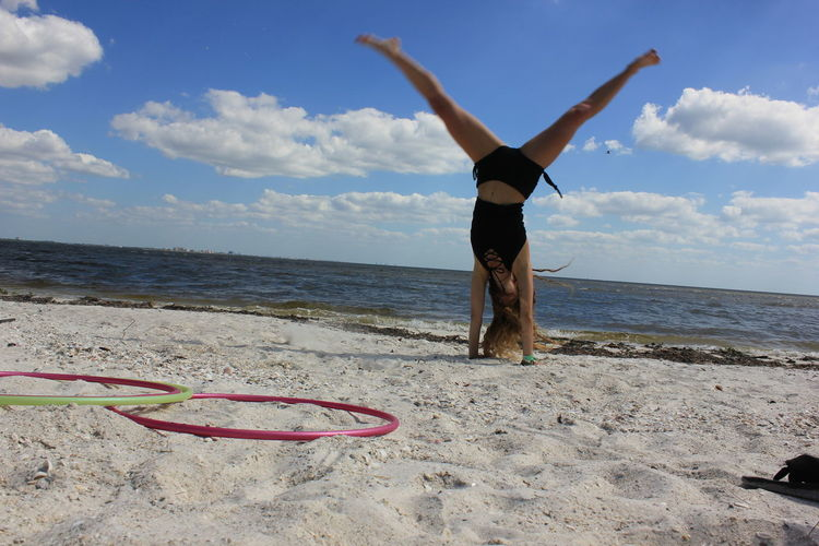 Full length of woman doing handstand at beach against cloudy sky