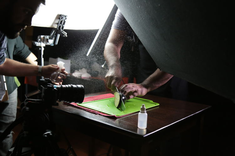 Man Filming Male Friend Cutting Eggplant On Table