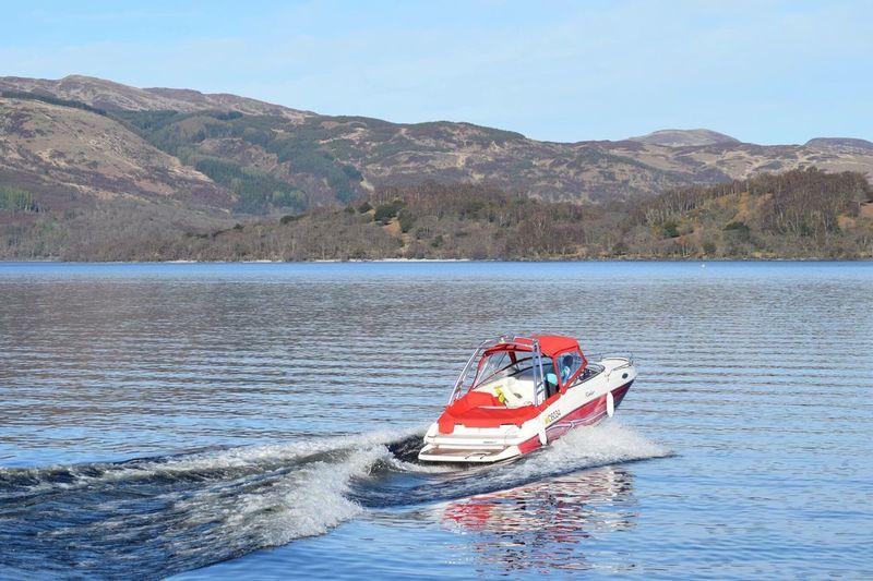 Motorboat In Lake Against Sky