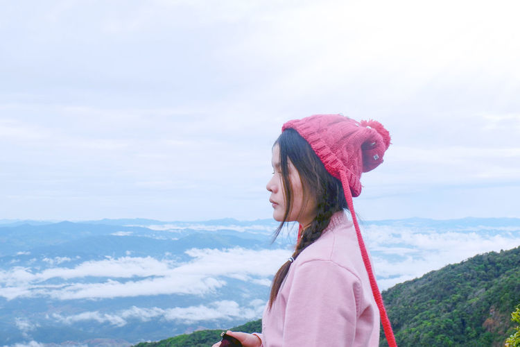 Side view of woman standing on mountain peak against cloudy sky