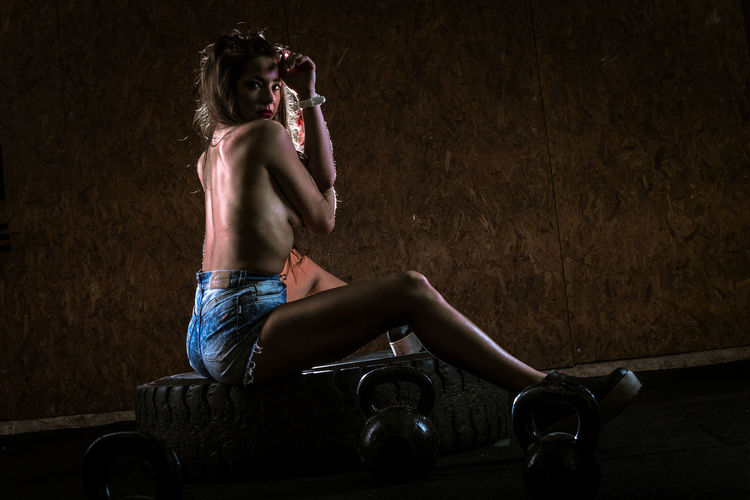 Rear view of shirtless woman sitting on tire at gym