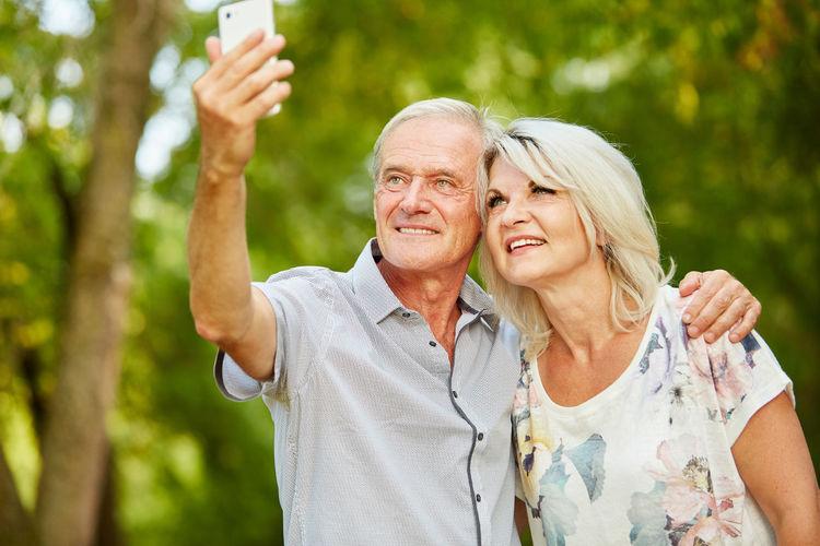 Senior Couple Taking Selfie At Park