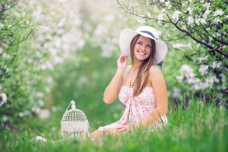 Women Springtime Fashion Outdoors Portrait Nature Flower Beautiful Woman Smiling Beauty Young Adult Pretty Spring Gorgeous Brunette Caucasian Happy Cage Females Blossom One Person Leisure Activity Sitting Grass Field International Women's Day 2019