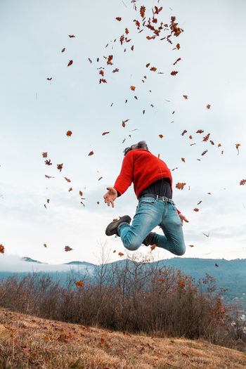 Rear view of man jumping on field against sky