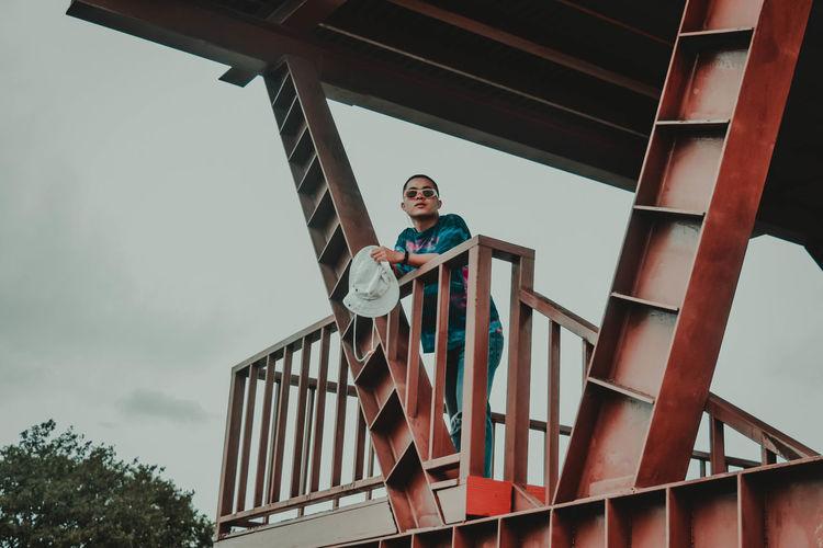Low angle portrait of teenage boy against sky