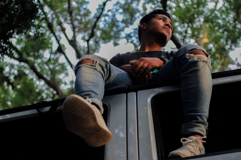 Low angle view of thoughtful young man looking away while sitting on car roof against trees