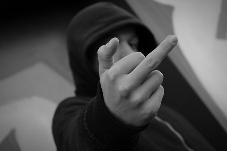 Man showing obscene gesture while standing against wall