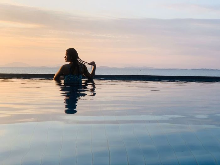 Rear view of woman in infinity pool against sky during sunset