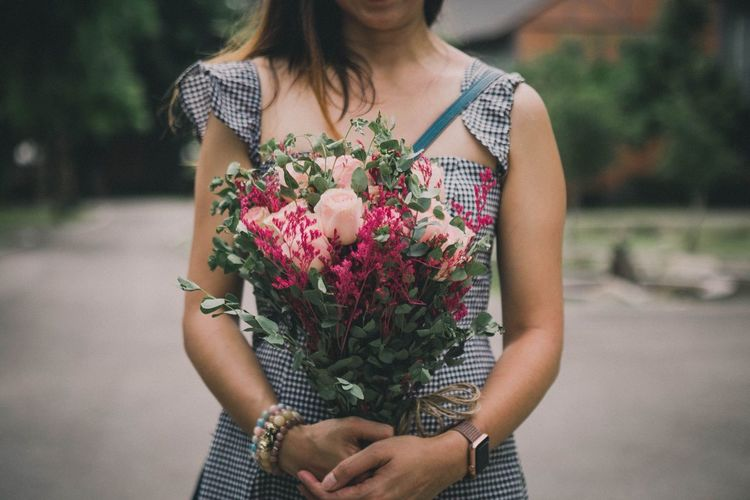 Midsection of woman holding flower bouquet while standing on footpath