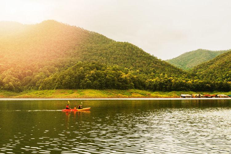 People on boat in lake against sky