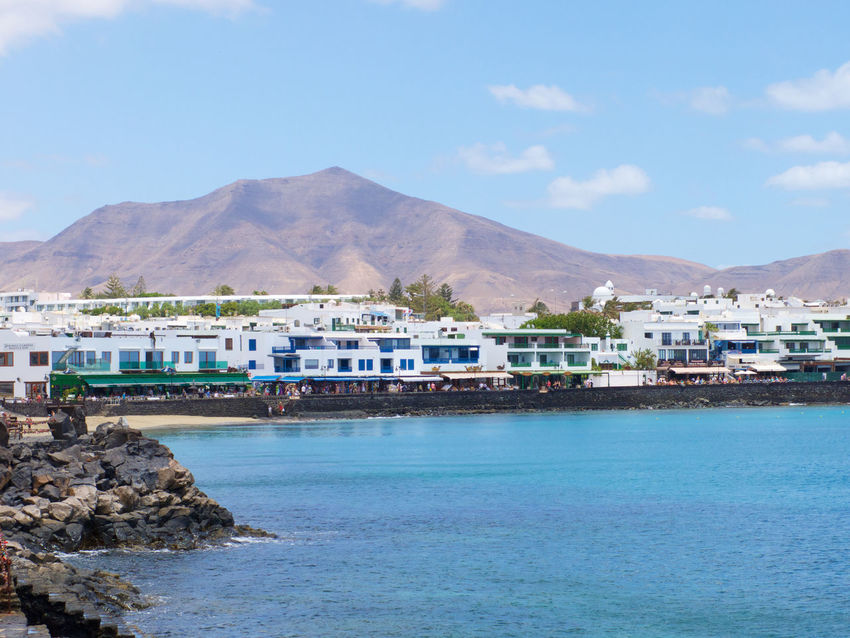 The seafront buildings of Playa Blanca on the Spanish island of Lanzarote. Architecture Blue Landscape Lanzarote Mountain Mountain Range Outdoors Playa Blanca Scenics Sea Sea Front Seafront Seafront Views Sky Town Tranquil Scene Water Waterfront