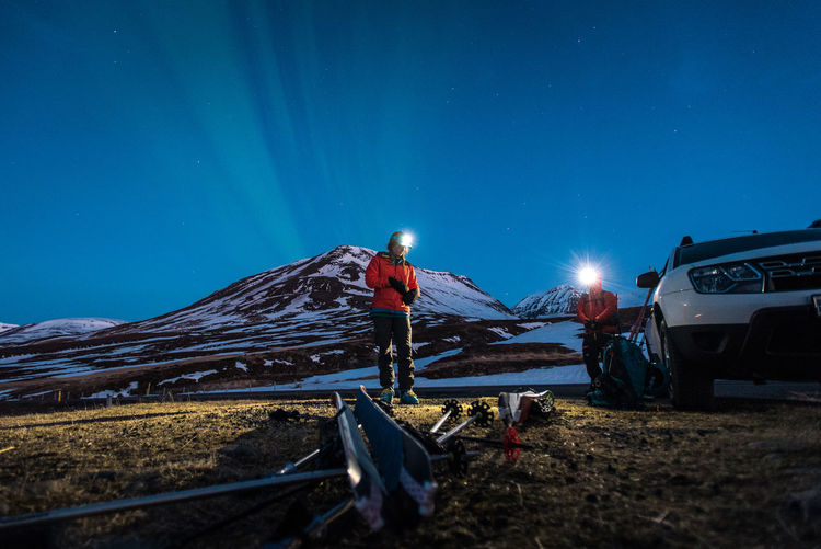 Man working on snowy field against blue sky at night