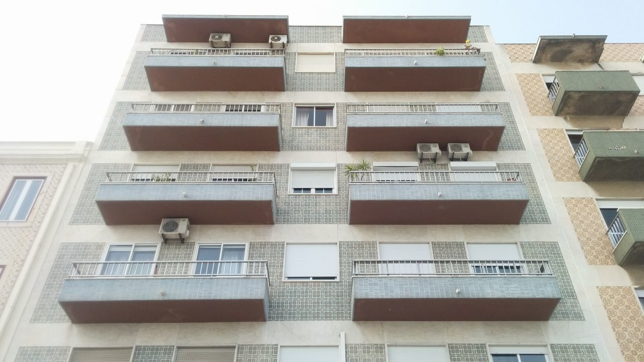 architecture, building exterior, built structure, window, low angle view, residential building, no people, apartment, city, balcony, air conditioner, day, outdoors