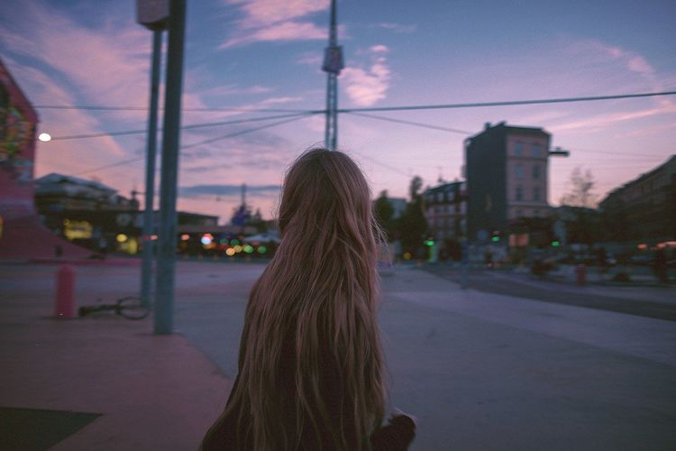 Rear View Of Girl With Long Hair On Sidewalk