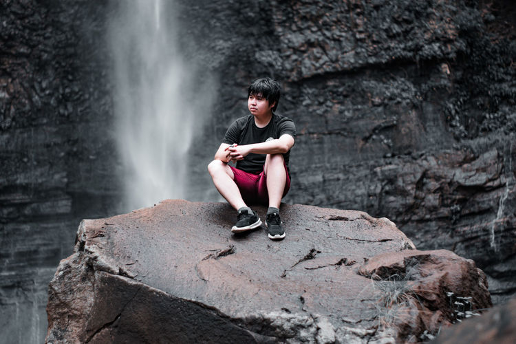 Full length of man sitting on rock against waterfall