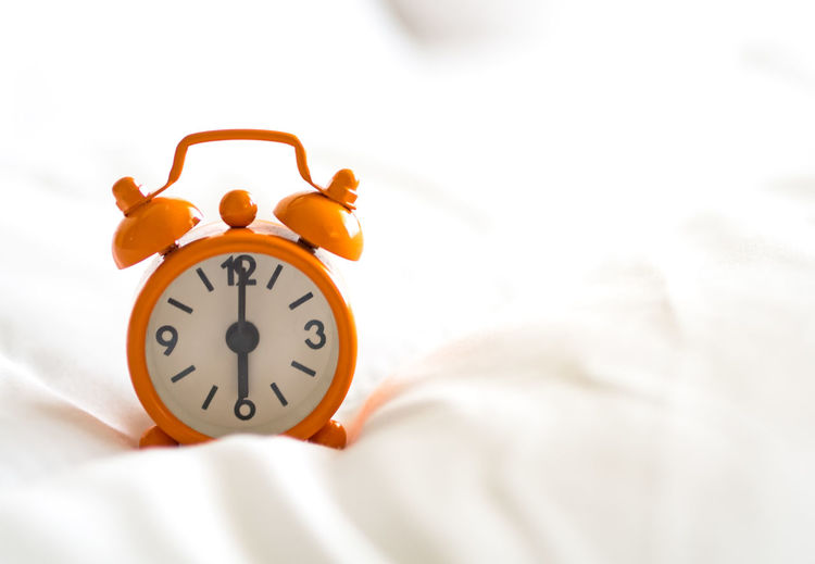 Close-up of clock on bed