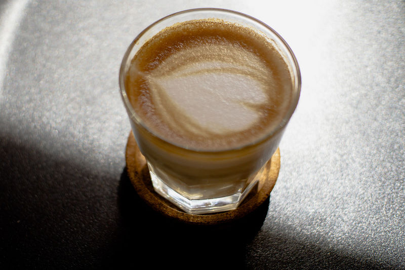 Coffee latte art heart shape under sunlight with black background, Black Background Coffee Shop Coffee Time Cork Nature Light Close-up Coffee Coffee - Drink Drink Drinking Glass Food And Drink Freshness Frothy Drink Glass Heart Shape High Angle View Hot Drink Household Equipment Indoors  Latte Latte Art Milk No People Non-alcoholic Beverage Refreshment Still Life Sun Light Table