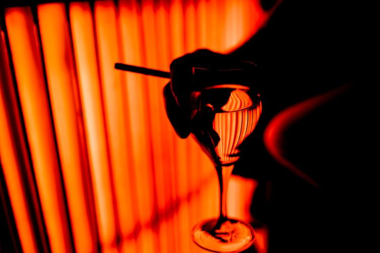 Cropped image of person holding wineglass and cigarette at nightclub in dark