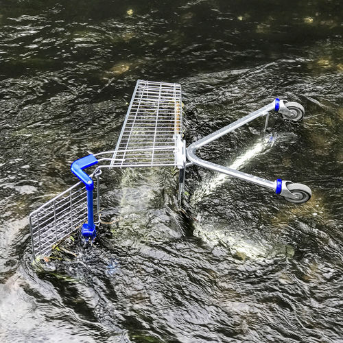 Vandalised supermarket shopping trolly thrown into river Anti Social Basket Behaviour Cart Chrome Conceptual Day Drowning Environment Environmental High Angle View Metalic Motion No People Outdoors River Shiny Shopping Shopping Cart Trolly Vandalism Water Waterfront