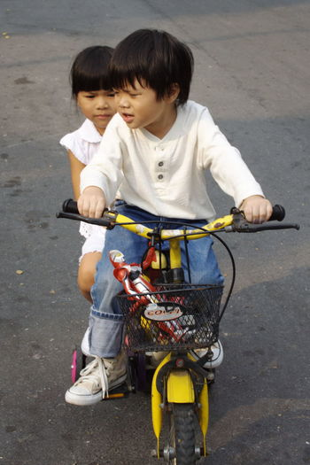 Cute Boy Riding Tricycle With Sister On Road