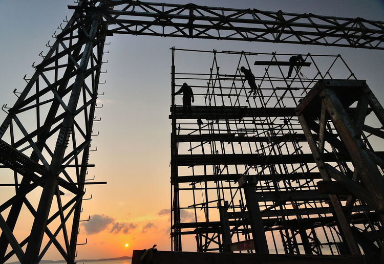 Low Angle View Of Workers On Silhouette Scaffolding Against Sky During Sunset