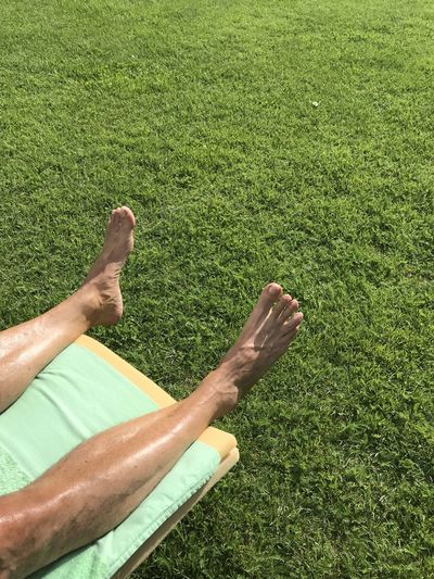 Low section of person relaxing on field