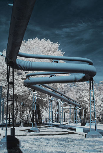 Snow covered metal structure against sky during winter