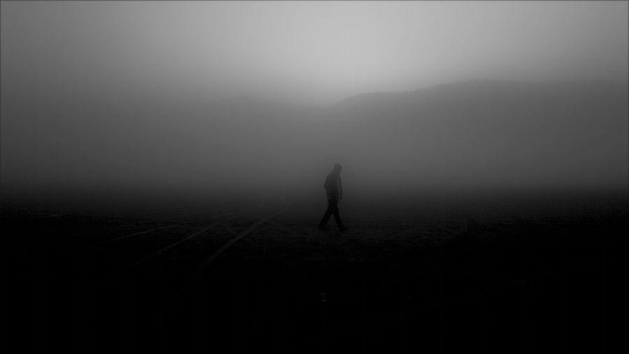 Silhouette people walking on landscape against sky
