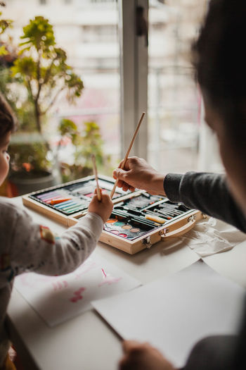 Mother and daughter painting on table