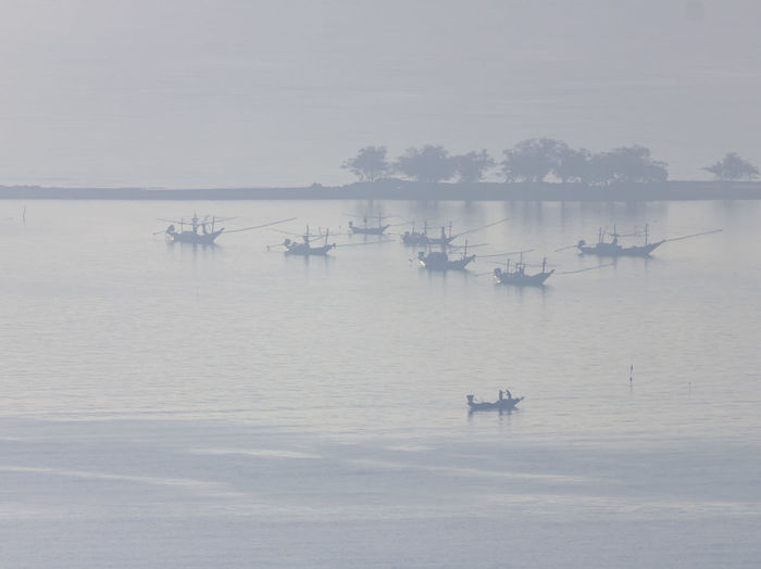 Shallow fishing boats park at the beach on foggy days. Water Transportation Nautical Vessel Mode Of Transportation Sky Waterfront Scenics - Nature Fog Beauty In Nature Nature Tranquil Scene Tranquility Sea Day Travel Reflection No People Outdoors