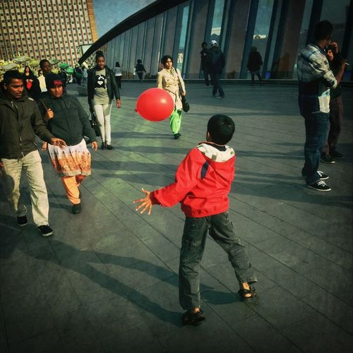 Child playing with red balloon.
