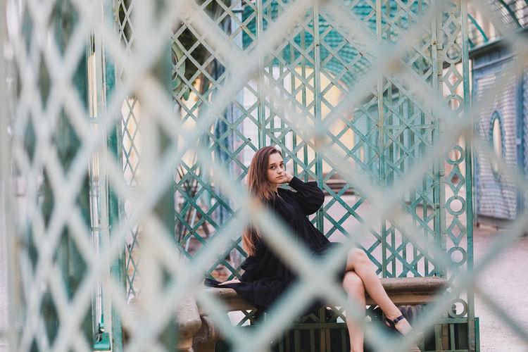 Portrait of woman seen through metal gate