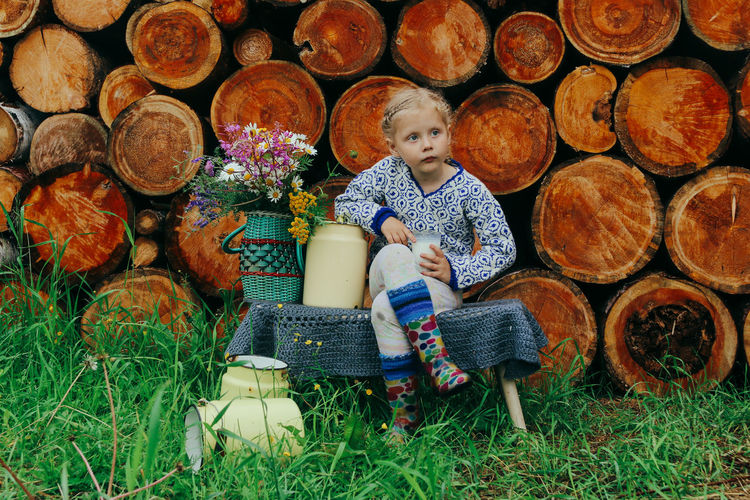 Full length of a boy sitting on logs