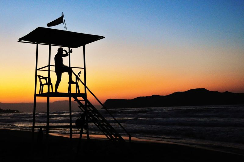 Full length of silhouette lifeguard on hut at beach against clear sky during sunset