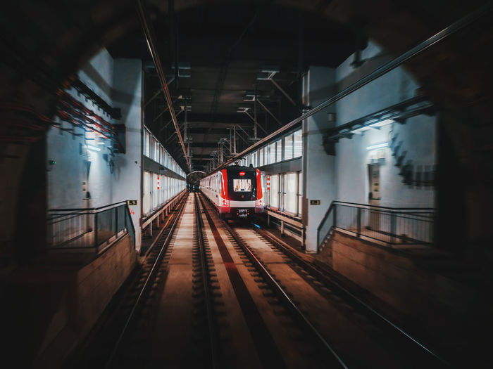 Train at railroad station platform seen through tunnel