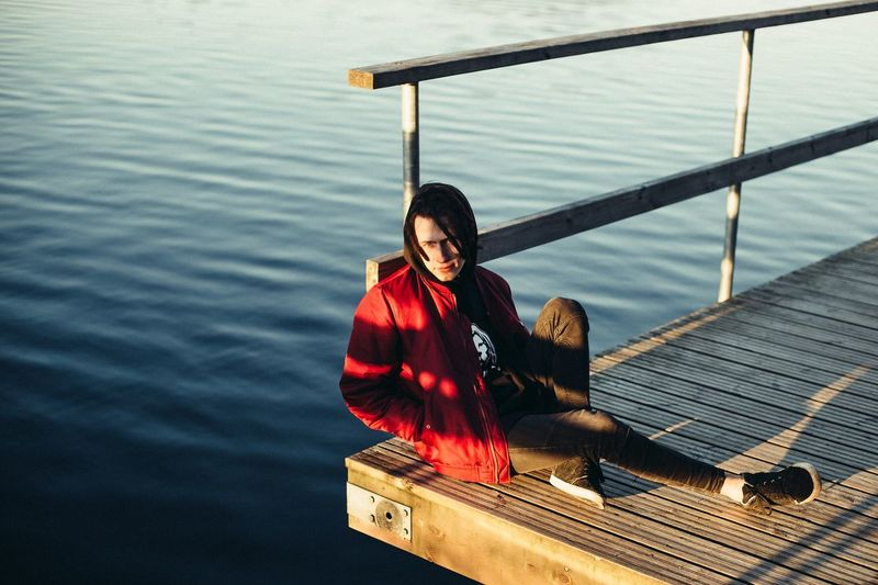 High angle view of woman sitting on pier over lake
